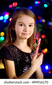 Christmas portrait of happy little girl by a fireplace in a cozy dark living room on Xmas eve