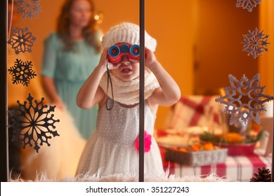 Christmas portrait of little funny girl looking through the window with binoculars, waiting for Santa