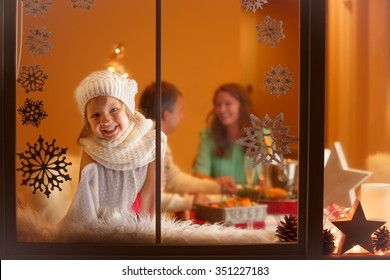 Christmas portrait of little girl looking through the window, waiting for Santa