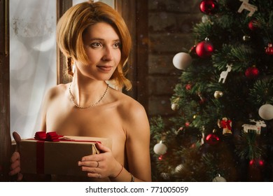 Christmas portrait of the red-haired girl at window of old house with gift in hands.