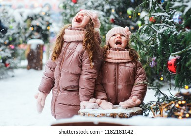 Christmas portrait of two happy sisters playing outdoor in winter snowy city decorated for New Year holidays. Kids spending Christmas vacations outdoor and traveling