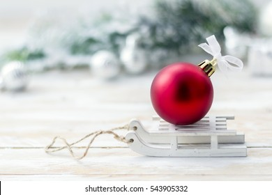 Christmas postcard with big red ball on sleigh, fir tree and silver balls on white wooden background