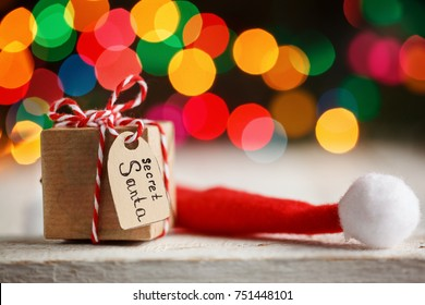 Christmas present or box for secret santa with Santa hat on colorful bokeh background.