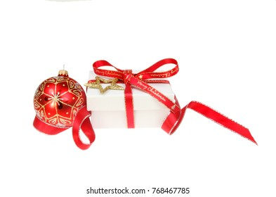 Christmas present decoration, box tied with Merry Christmas ribbon surrounded with red ribbon and with gold glitter star and a red bauble isolated against white