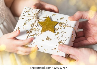Christmas present, father and daughter, hands holding white gift with golden star, selective focus.
