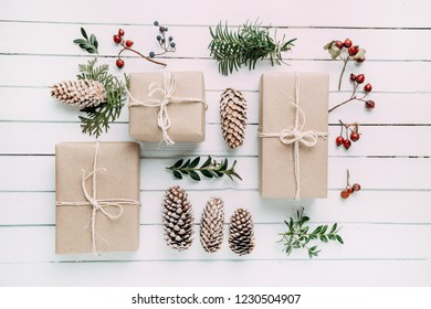 Christmas present or gift box on the wood table. Wrapped vintage craft paper gift box decorated with sprig of Christmas tree.