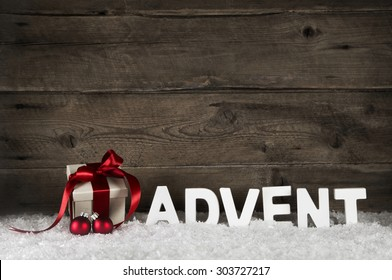 Christmas present or gift with classical red ribbon or bow on rustic wooden background with the letters advent for decorations.