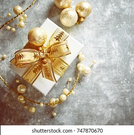 Christmas present with golden ornaments on gray background. Christmas background. Top view. Copy space.
