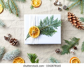 Christmas present with natural decorations on linen  background. Flat lay