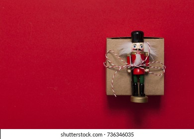 Christmas present with nutcracker on a red background