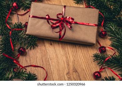 Christmas present on wooden board with fir tree, red bells. Red ribbon on paper gift box. Top closeup view with copy space.