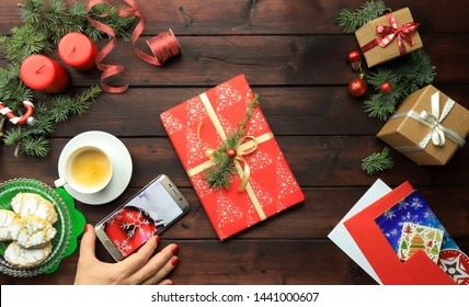 Christmas present on the wooden table with Christmas decorations, gifts and ornaments. Christmas workplace top view