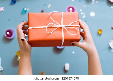 christmas present in red paper wrapping. hands holding a gift box. greeting surprise and reward concept.