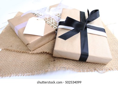 Christmas present with ribbon wrapped in kraft paper on white background