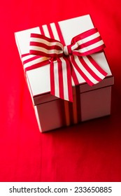 Christmas present wrapped in the box with red and white ribbon.