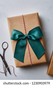 Christmas present wrapped in brown paper with twine, bow and scissors. View from above