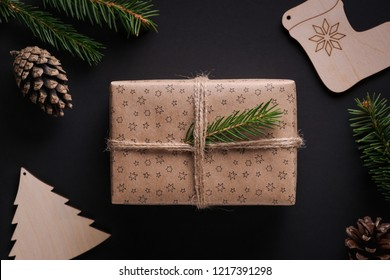 Christmas present wrapped in craft paper with twine, decorated with green spruce twig on black background, surrounded by pine cones, branches and wooden decorations. Flat lay style