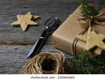 Christmas present wrapped in plain brown paper on a rustic wood table with holiday cookies, twine, scissors and greenery.