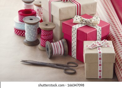Christmas present wrapping background, wooden vintage ribbons spools and gift boxes and wrapping paper rolls