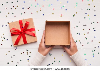 Christmas presents delivery service. Female hands with empty open gift box on white wooden background, top view, copy space