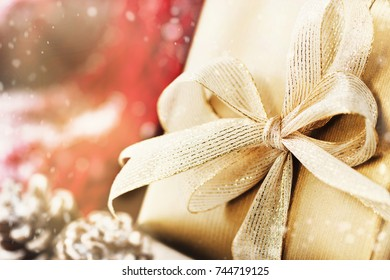 Christmas presents or gifts with elegant bow and christmas decorations on bright snowy background, christmas concept, closeup