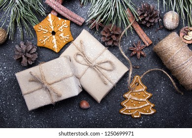 Christmas presents, gingerbreads, pine twigs and cones covered with snow on dark background