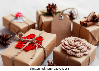 Christmas presents with hand made decorations - crocheted flower and snowflake, pine cones, vanilla pods. DIY New Year decorations for wrapped in craft paper gifts.