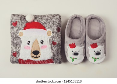 Christmas presents. Knitted sweater, slippers and hot chocolate with marshmallow laid on a white wooden table background. Flat lay. Top view. Toned