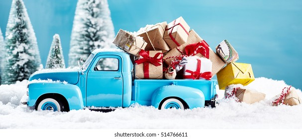 Christmas presents on blue truck falling from bed in the snow. For xmas concepts.