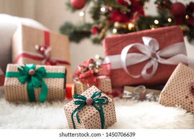 Christmas presents on light background on wooden table with cozy rug. Colorful ribbons. Christmas decoration. Happy Holidays