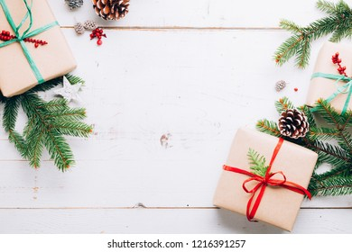 Christmas presents with paper craft, raffia bows, fir branches pin cones and  red berries on a white wooden table. Flat lay, copy space