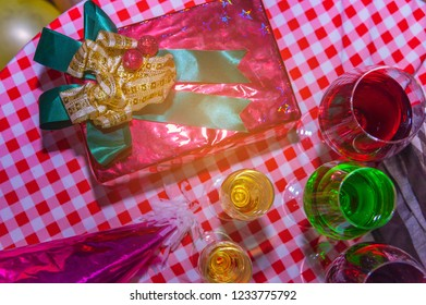 Christmas presents with red ribbon laid on a wooden table with glasses of wine