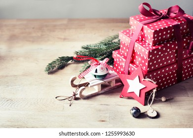 Christmas presents with red ribbon on dark wooden background in vintage style