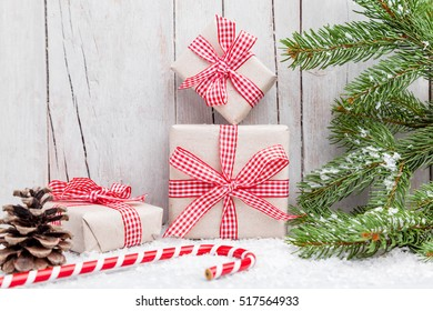 Christmas presents with snow on grey wooden background