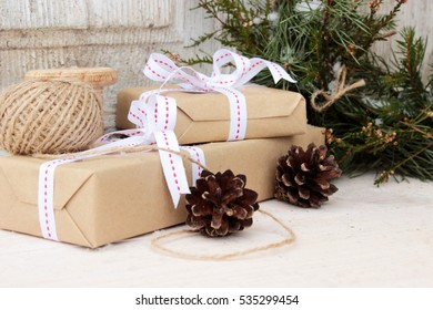 Christmas presents theme: very cute small gift boxes wrapped with simple rough paper and decorated with bright white ribbons, traditional green wreath made from natural wild plants and some piny cones
