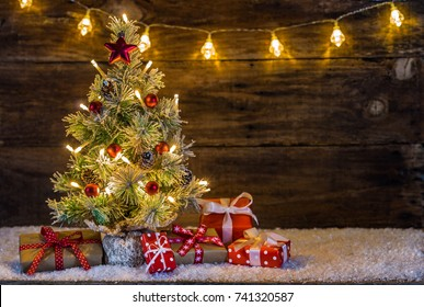 Christmas presents under decorated Christmas tree on snow with festive lights and wooden background
