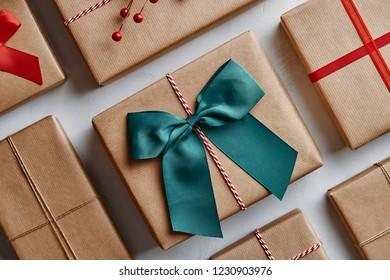 Christmas presents wrapped in brown paper and decorated with bows and ribbons. From above