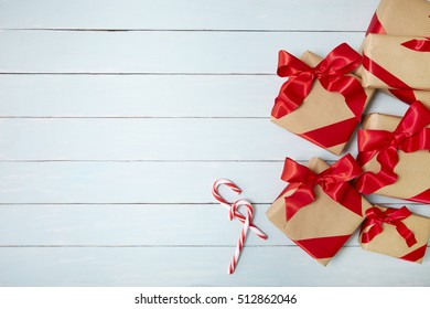 Christmas presents wrapped in brown paper with red silk bows on a painted wooden background, with candy canes and blank space at side