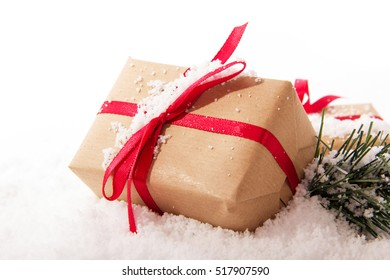 Christmas presents wrapped in brown paper with red ribbon