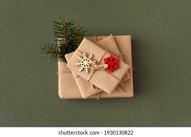 Christmas presents wrapped in ecological recycled paper with wooden decoration on green paper background - zero waste concept