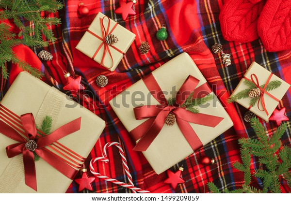 Christmas presents wrapped in kraft paper, ornaments, cones, fir branches and red mittens on Scottich tartan plaid blanket. Christmas, xmas, winter holidays concept. Top view.