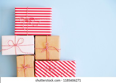 A lot of christmas presents wrappend in red, white and craft paper tied with baker's twine string. Multiple new years gifts in different wrapping. Top view, close up, copy space, background, flat lay.