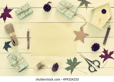 Christmas presents wrapping and empty card over wooden table with copy space. Vintage filtered