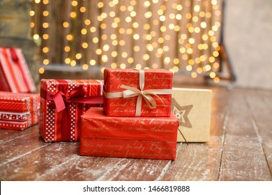 Christmas presents/gifts under fir-tree. Vintage New Year decorations. Red gift boxes and lantern under fir-tree on dark wooden flor. Christmas mood. Celebrating of New Year