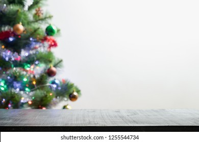 Christmas product background with blurred fir tree. Front shot of black wood table and backlit out of focus pine tree with garlands