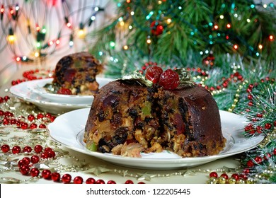 Christmas pudding in festive setting with Christmas tree and garland in background.