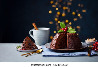 Christmas pudding, fruit cake with cup of tea. Traditional festive dessert. Dark background with lights garland. Copy space.