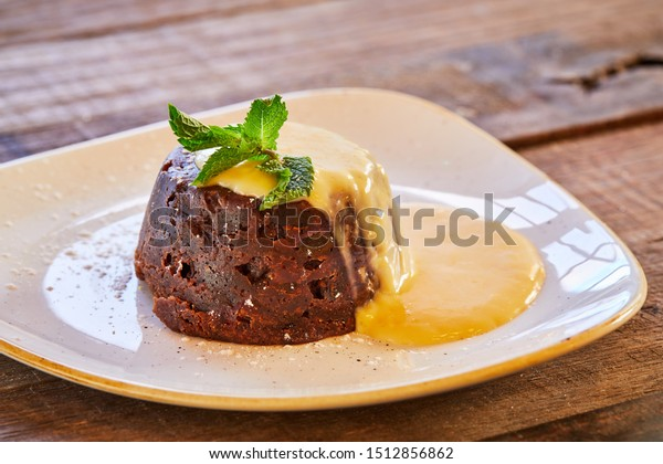 Christmas pudding served with custard and mint garnish