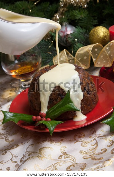 Christmas pudding with white vanilla sauce on holiday table, decorated with holly twig, glass of brandy, ornaments, candles, and xmas tree.