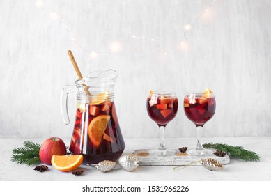 Christmas Punch or Sangria in pitcher and glasses with Christmas decoration on white table, copy space. Red wine fruit Christmas drink.